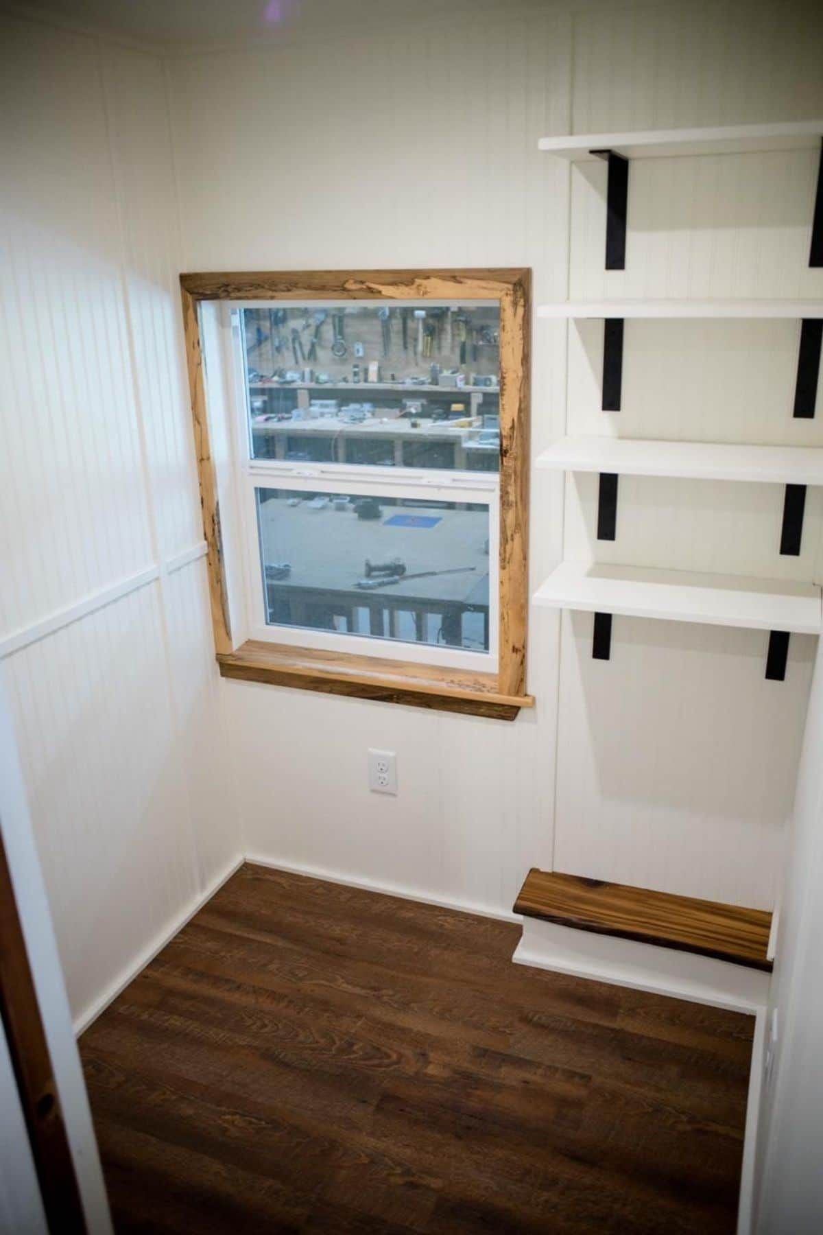 bedroom with shelves on wall and wood trimmed window