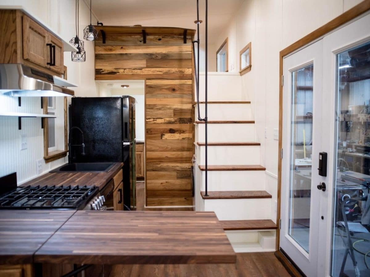 reclaimed wood wall next to stairs inside tiny kitchen