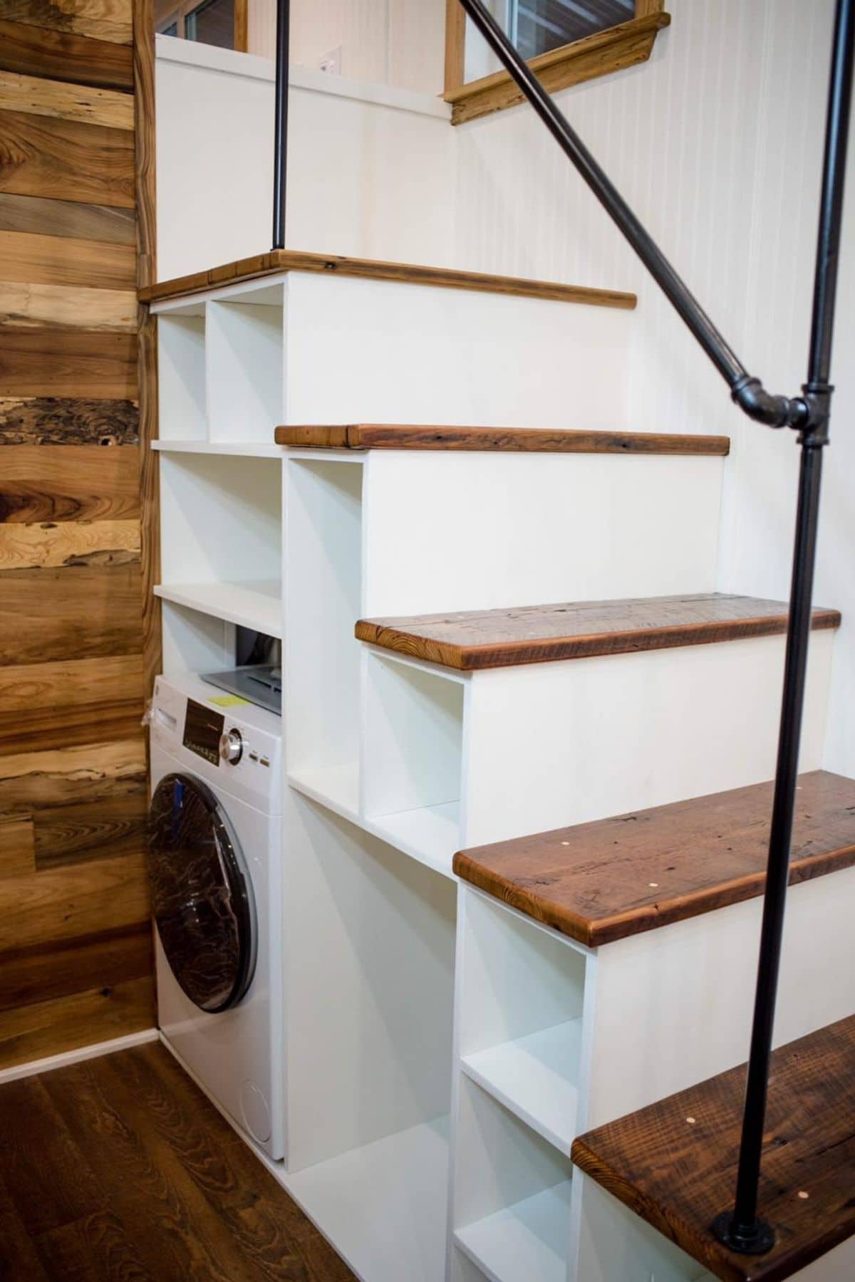 White stairs with cubbies holding washer