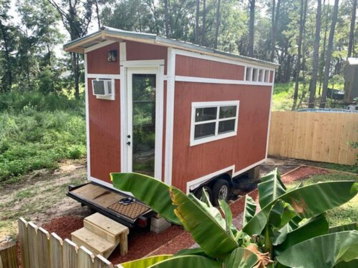 red tiny house with white trim by green plants