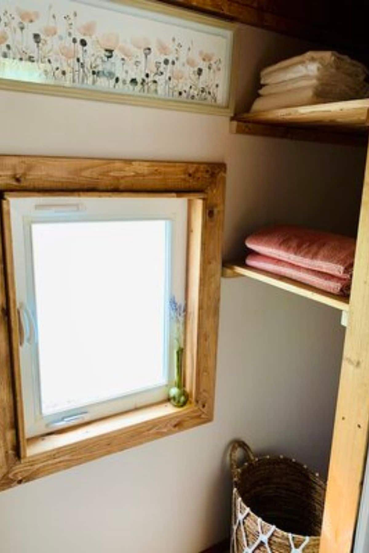 toiletry storage shelves by window in bathroom