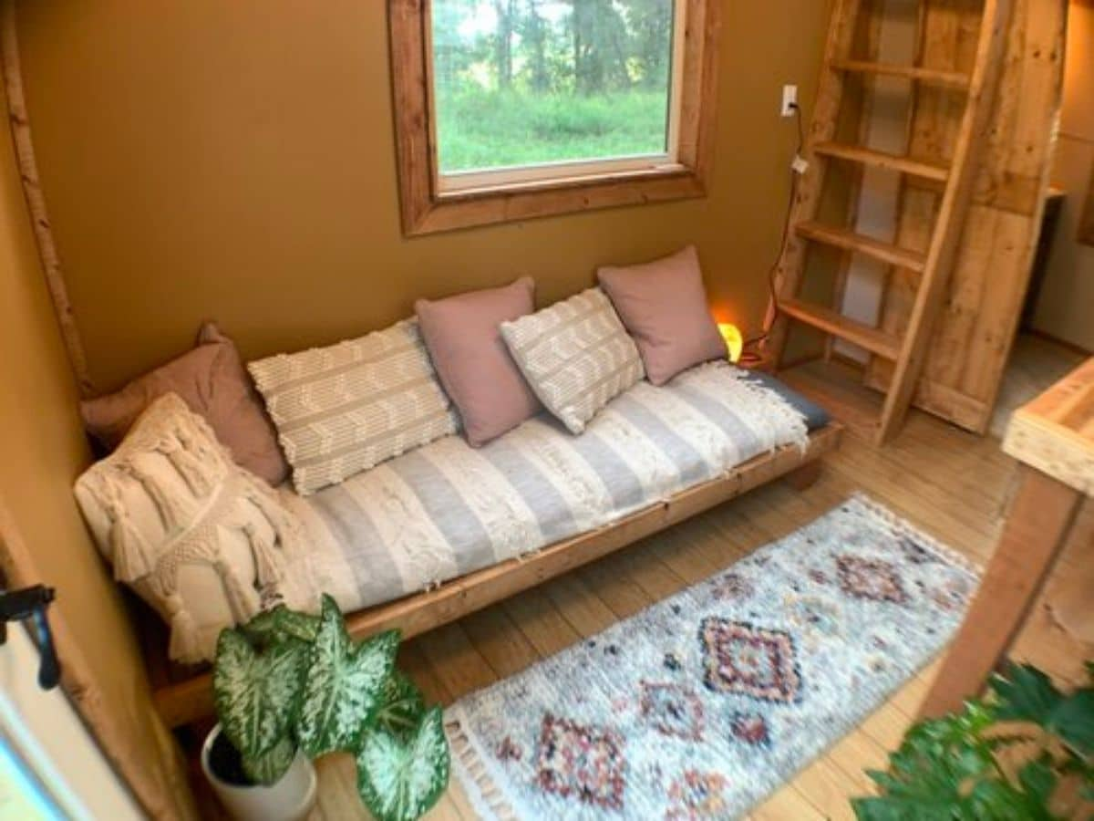 sofa against brown wall next to wood ladder
