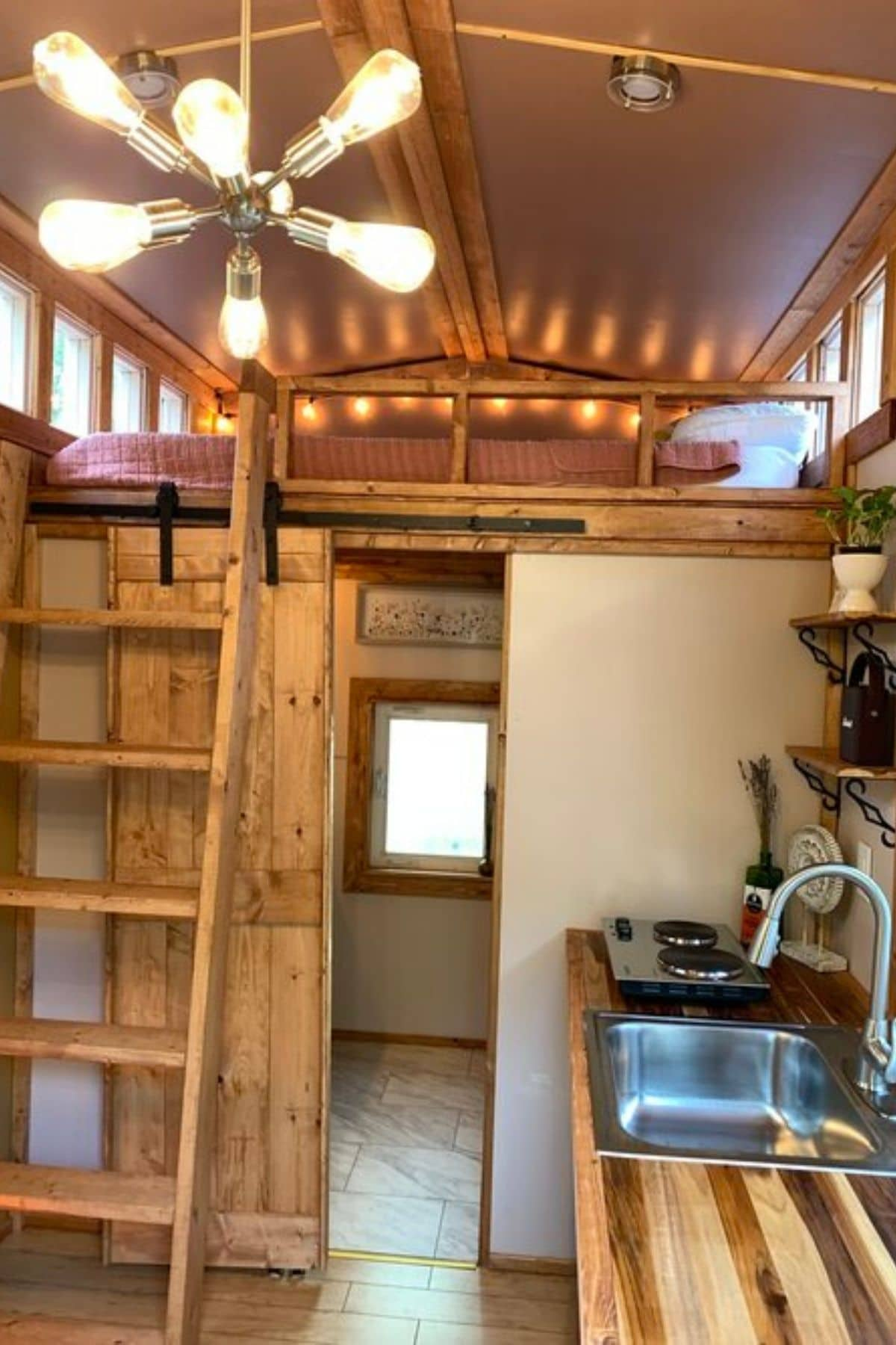 view from door into tiny home with loft behind butcher block kitchen counter