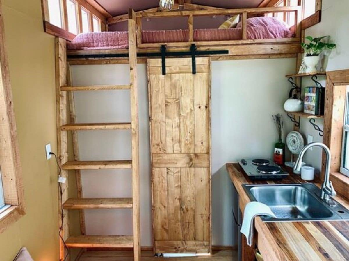 Kitchen counter on right of image with barn door at back of room and ladder to left