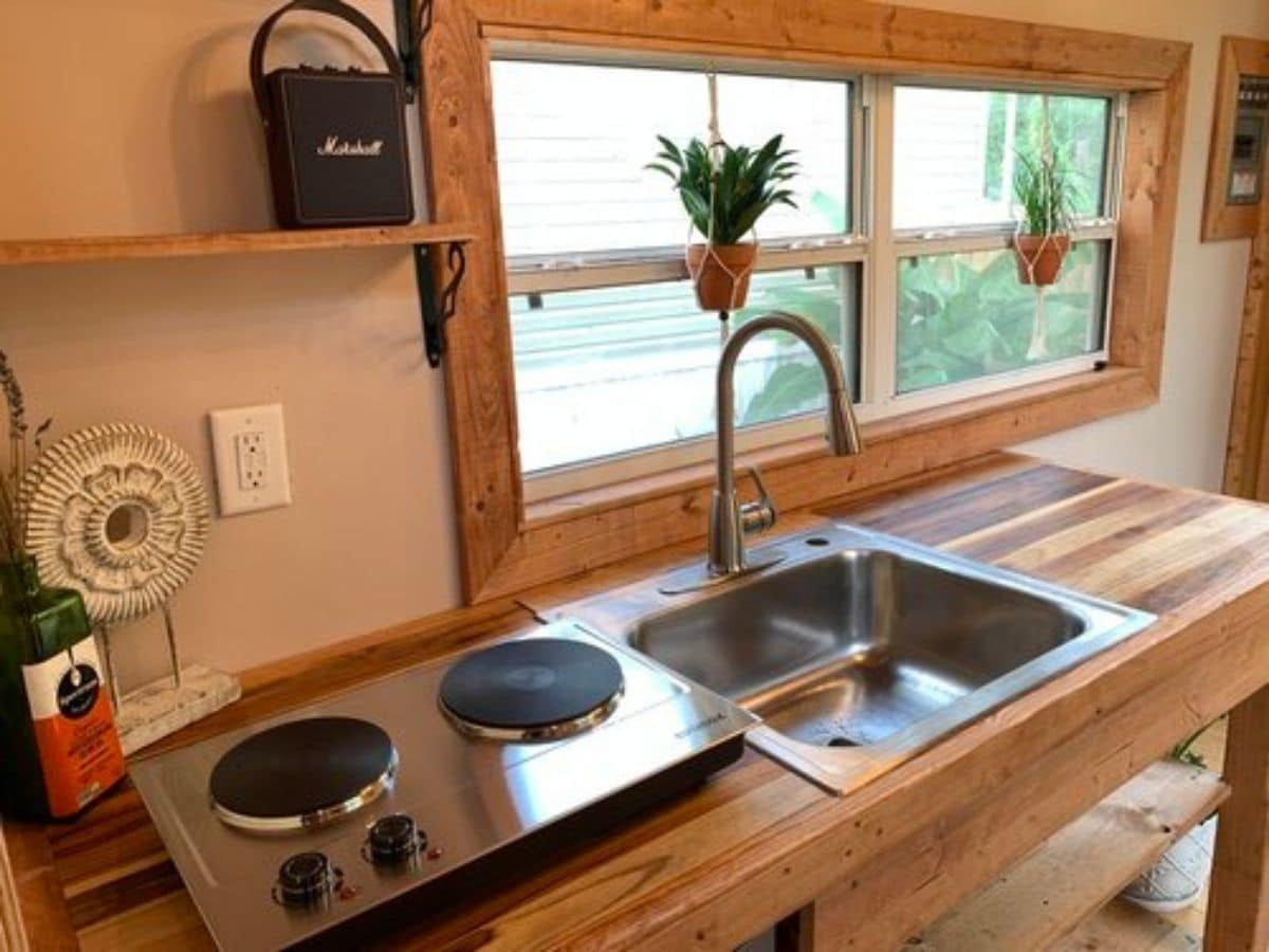two burner electric hotplate next to deep stainless steel sink in butcher block counter