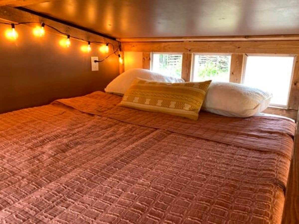 pink bedding on bed in loft under string of lights on wall
