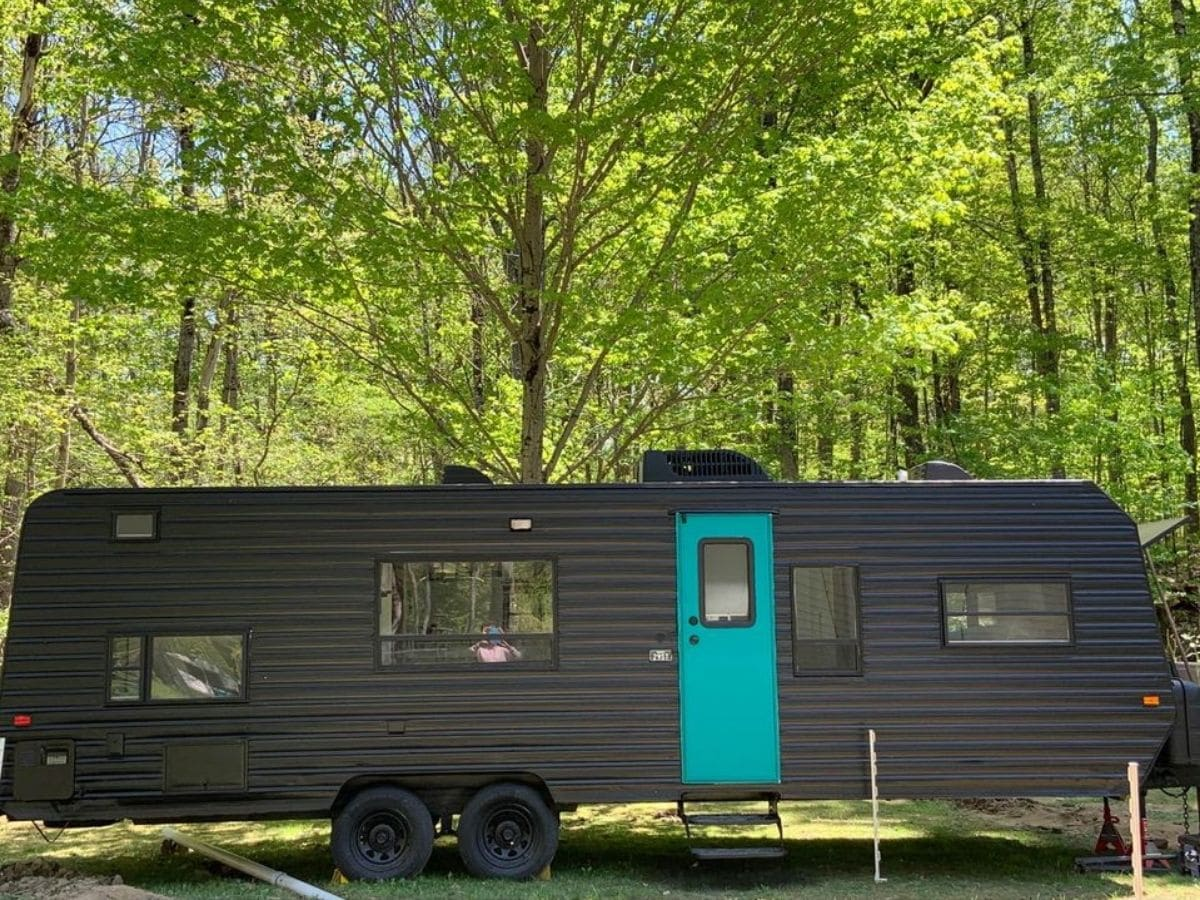Black RV with teal door parked against trees