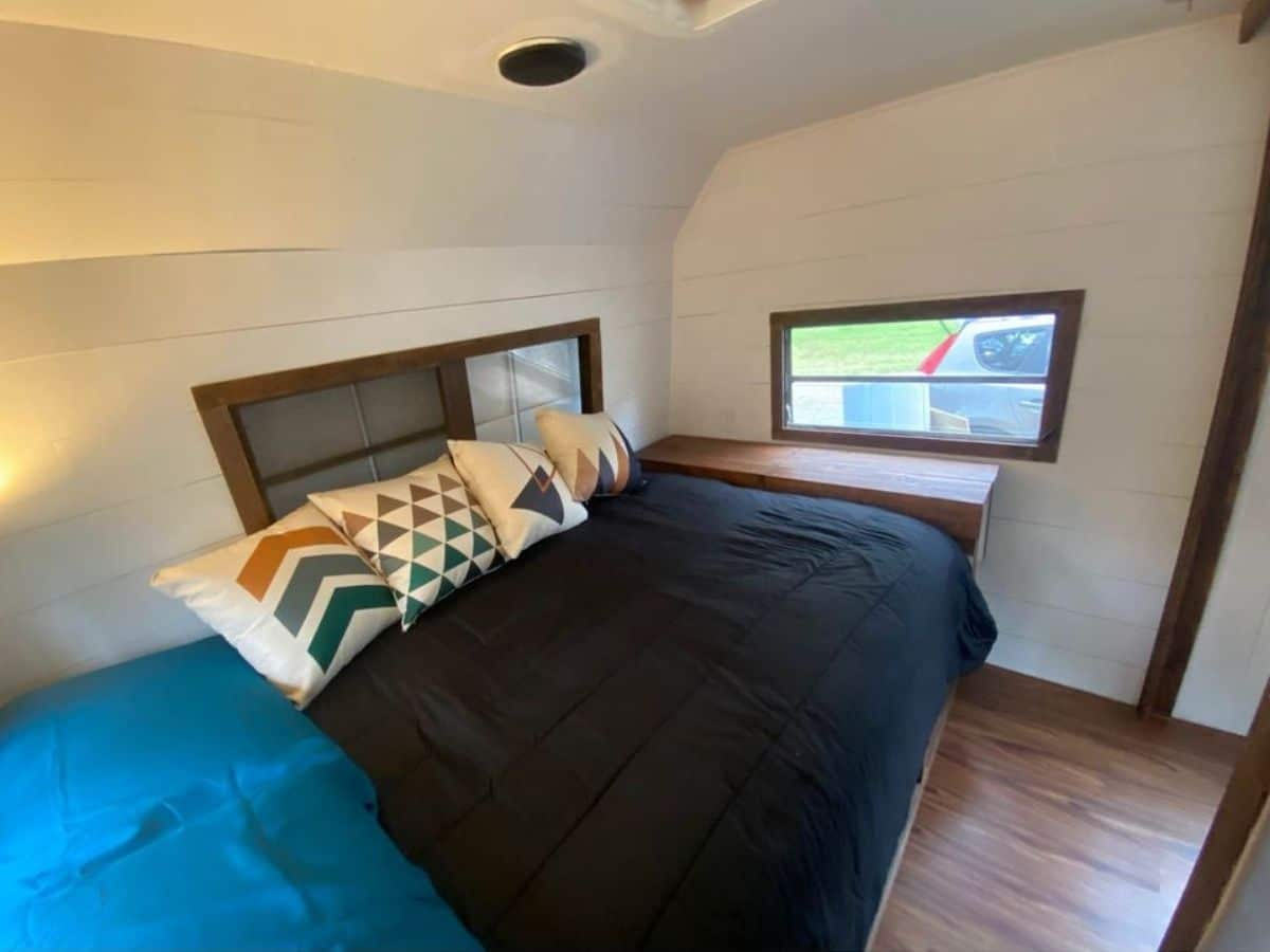 Black bedding on bed by windows with white walls
