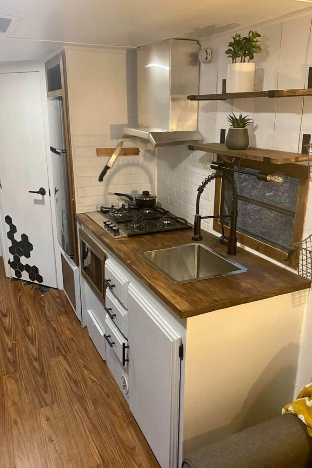 Kitchenette with sink and RV stove in white cabinets