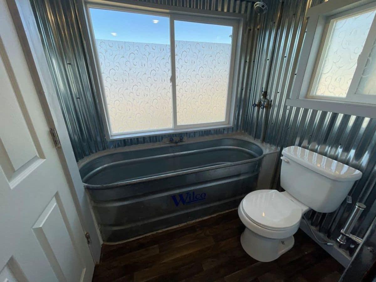 Galvanized metal bathtub and walls in tiny bathroom