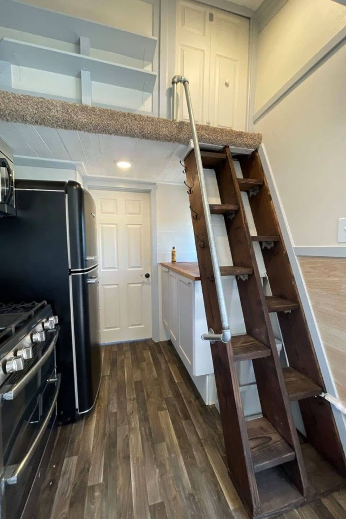Wooden stairs up to carpeted loft on right side of kitchen