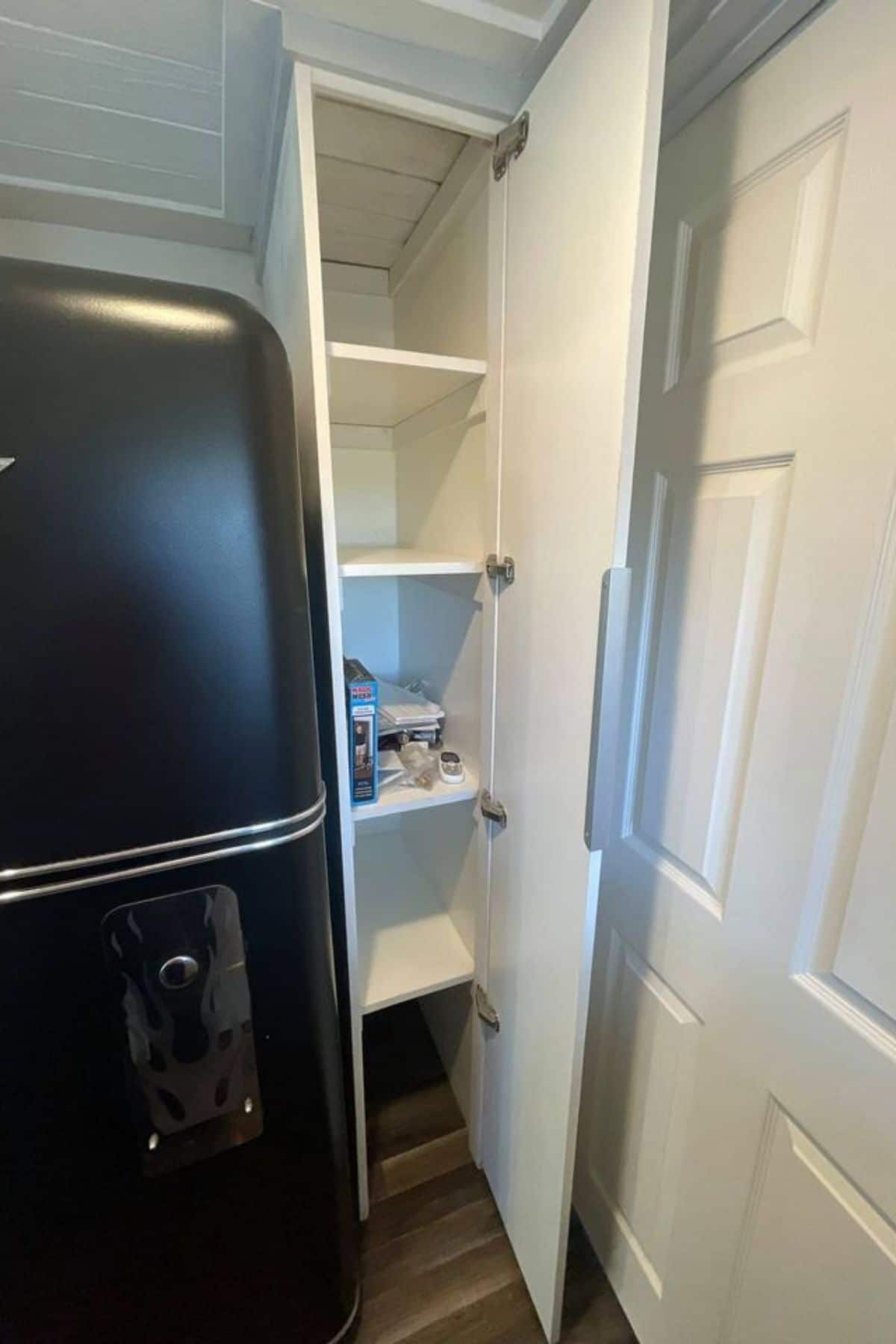 Open slim pantry beside black refrigeartor