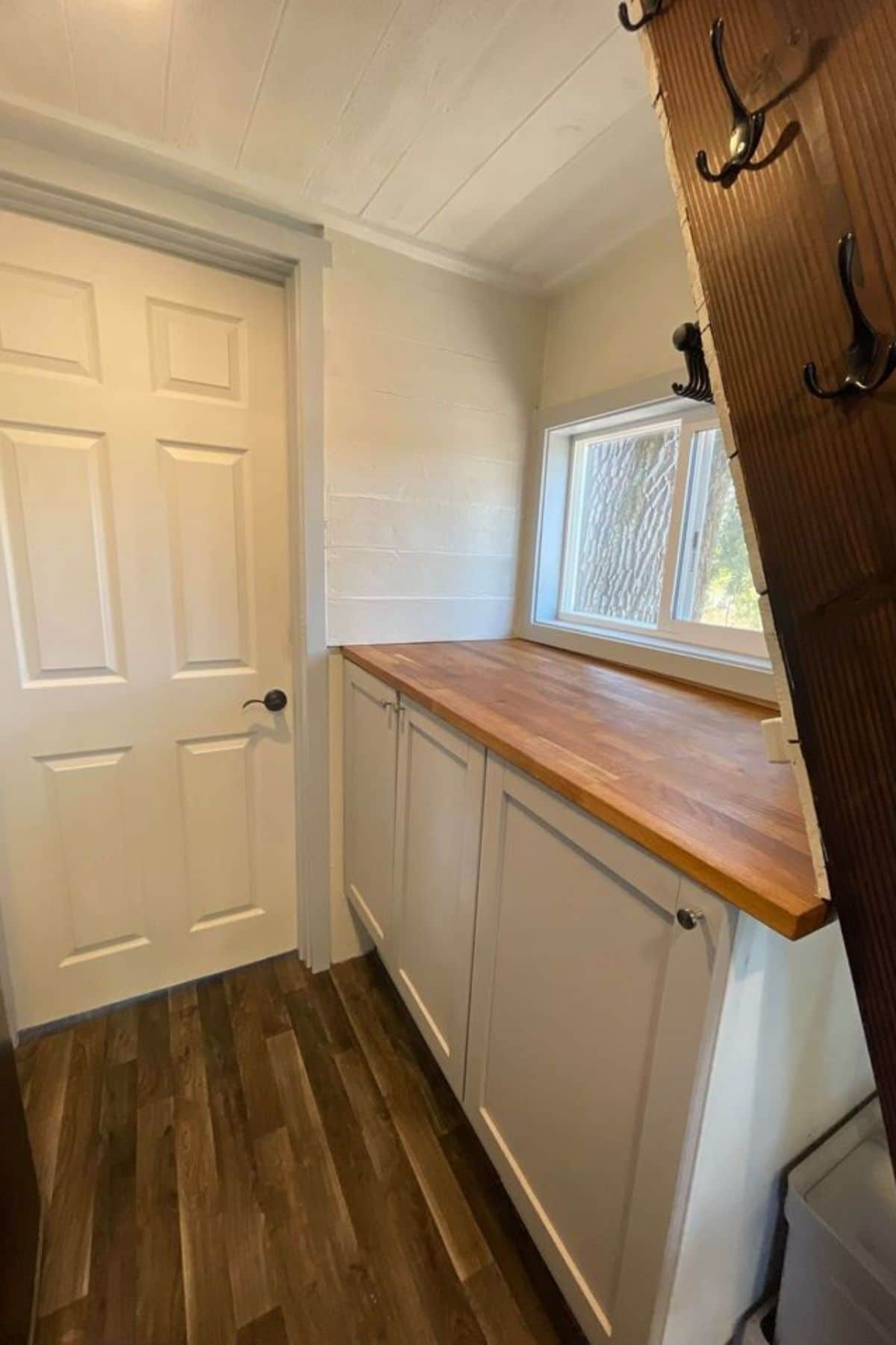 Storage cabinet with butcher block top next to white bathroom door