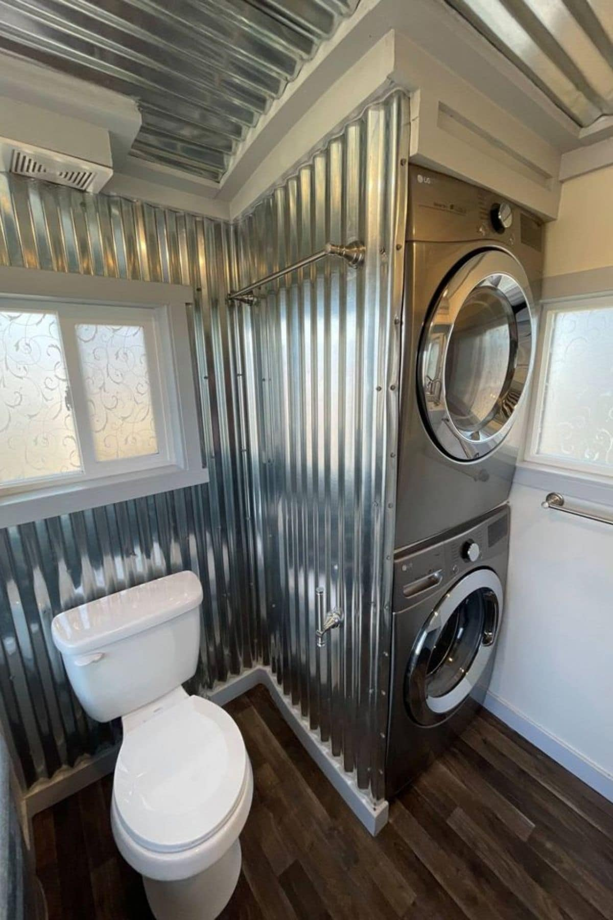 White toilet against metal wall with stainless steel stacking washer and dryer to the side