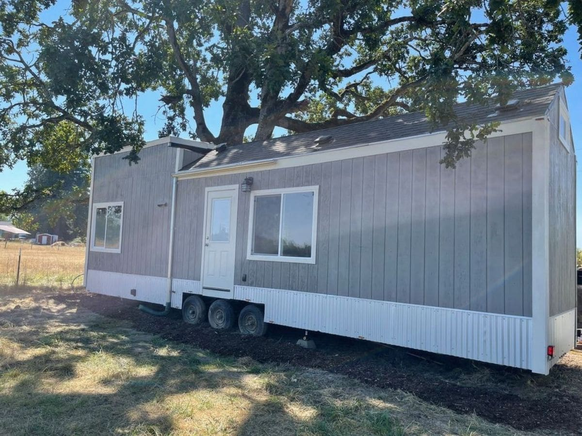 Tiny house on wheels with gray siding and white trim