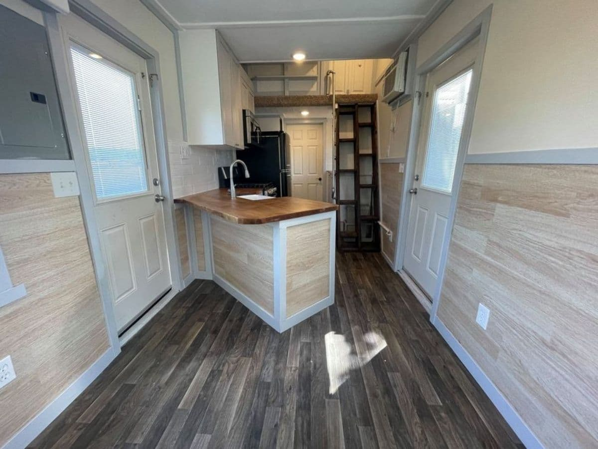 View into kitchen of tiny home with angled kitchen counter by door