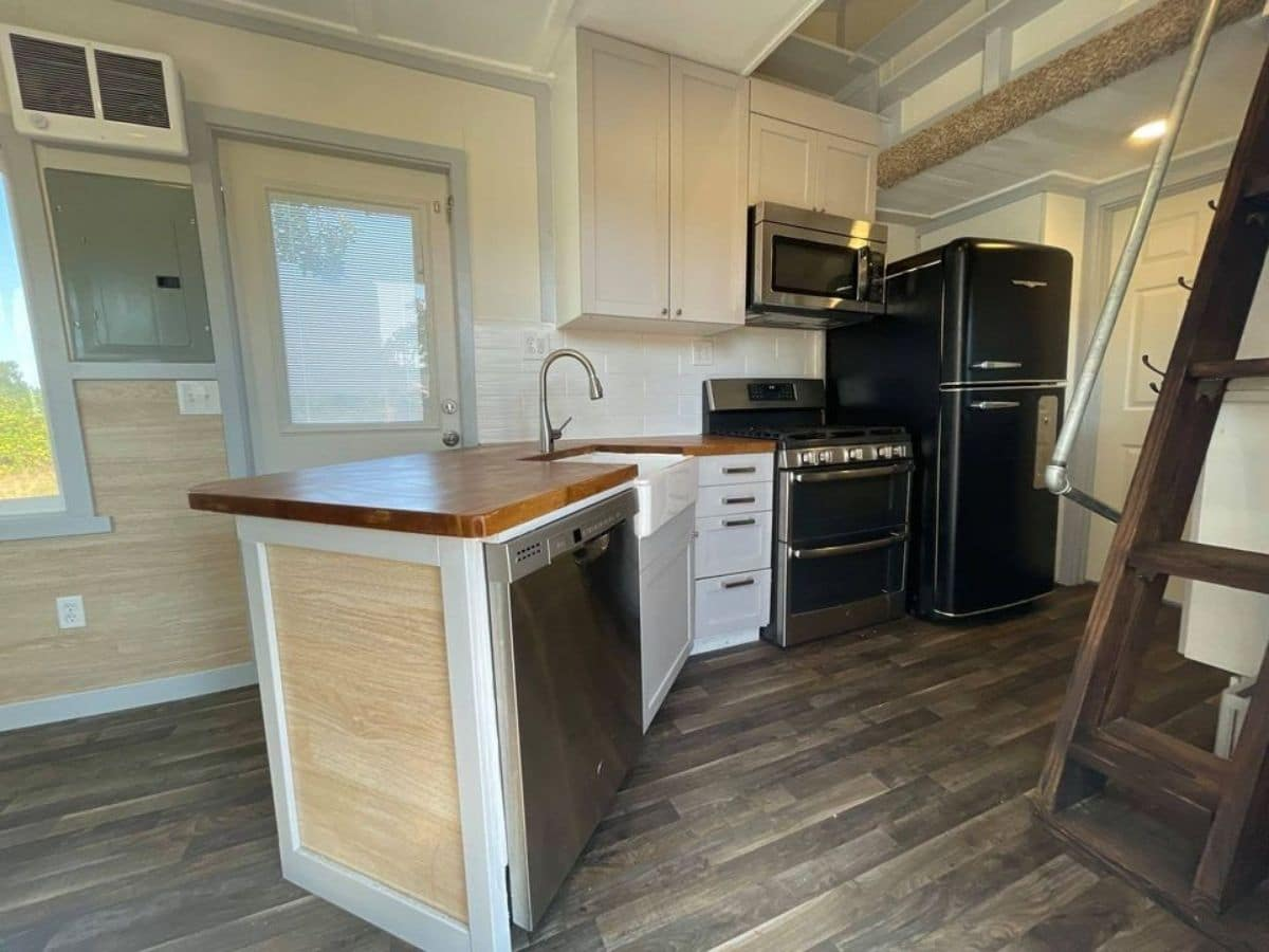 Angled kitchen counter with full-sized dishwasher stove and refrigerator
