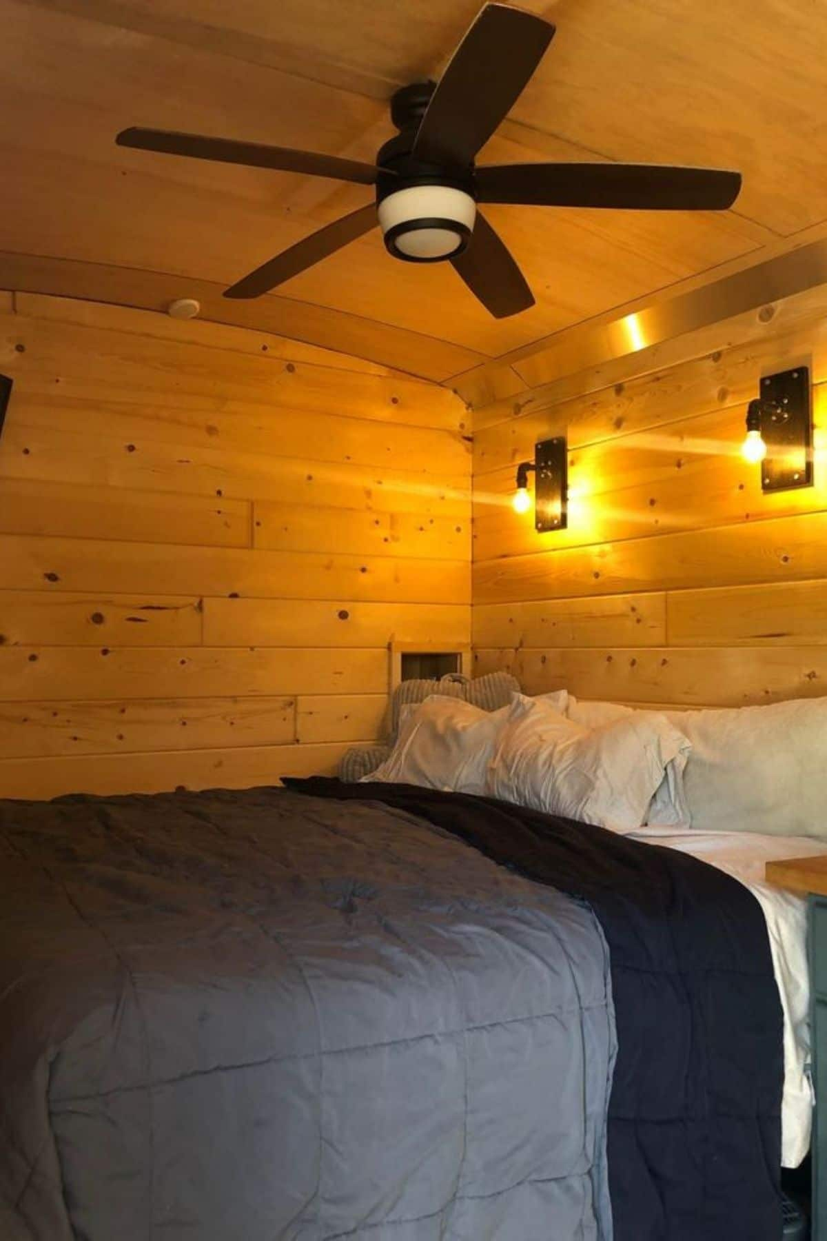 Bed against wall with two wall mounted lights and ceiling fan above