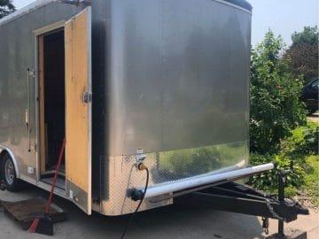 End of silver cargo trailer on driveaway with door open