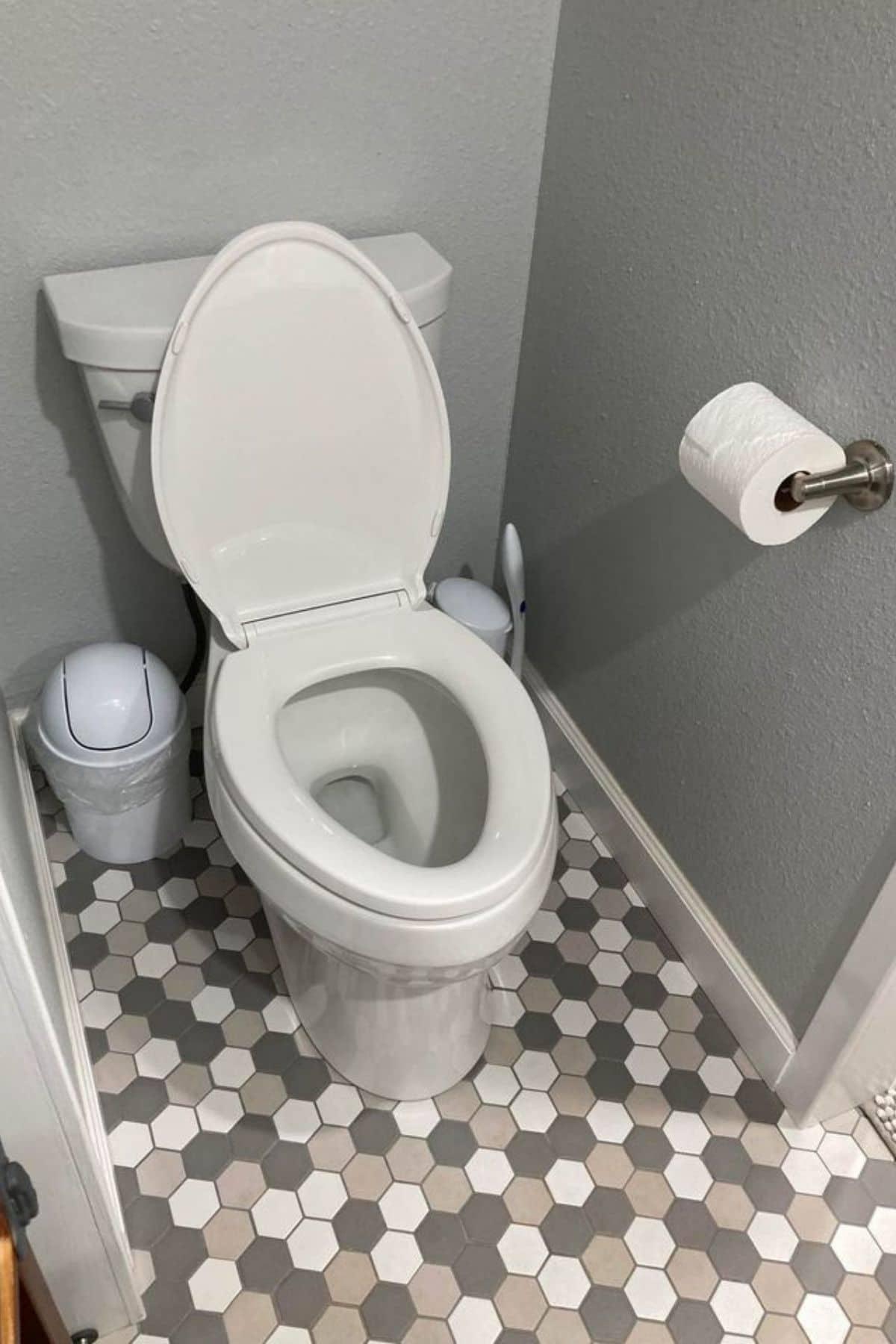 Gray and white round tile floor beneath flush toilet