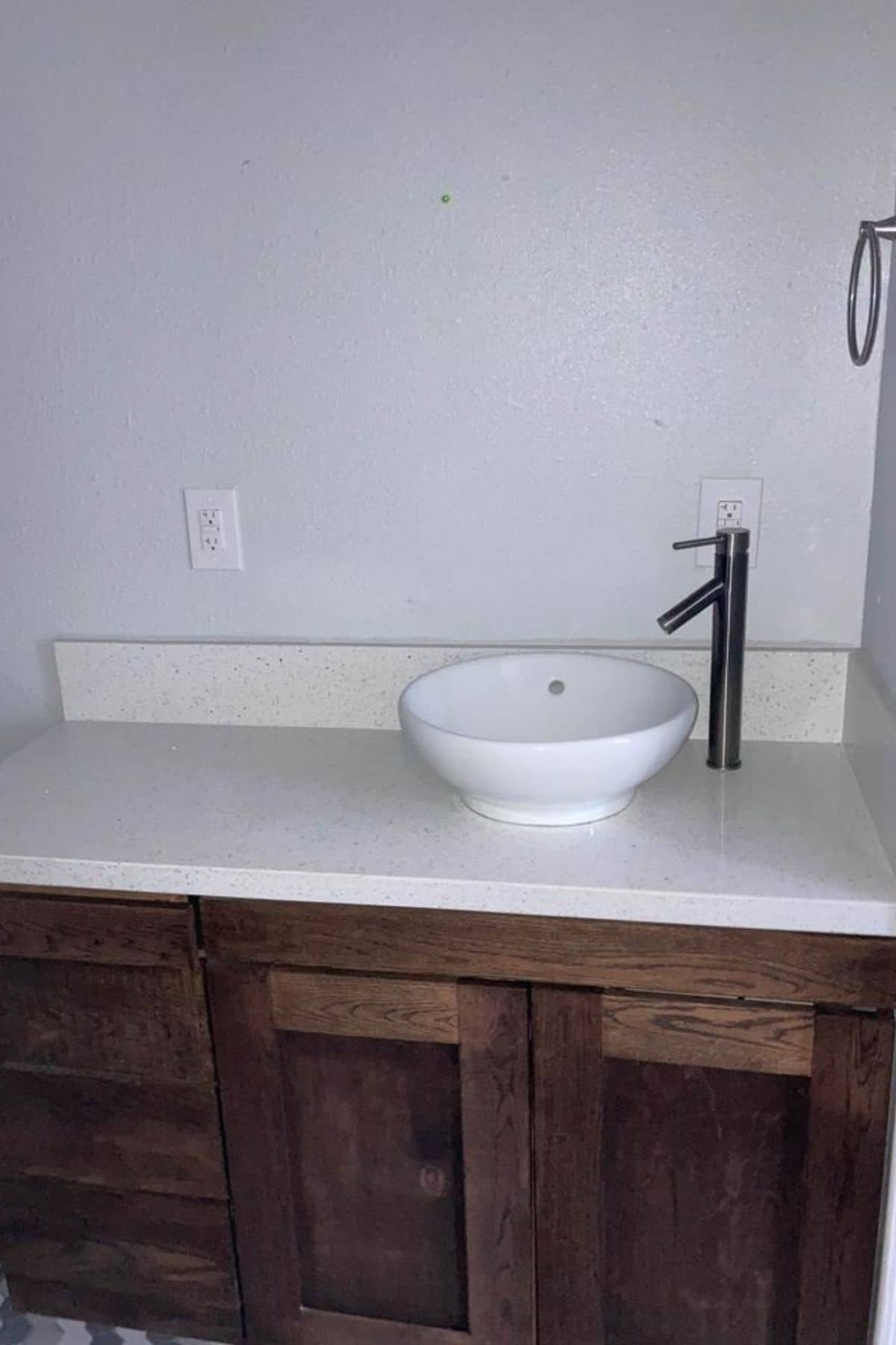Long bathroom counter with white bowl sink against white wall