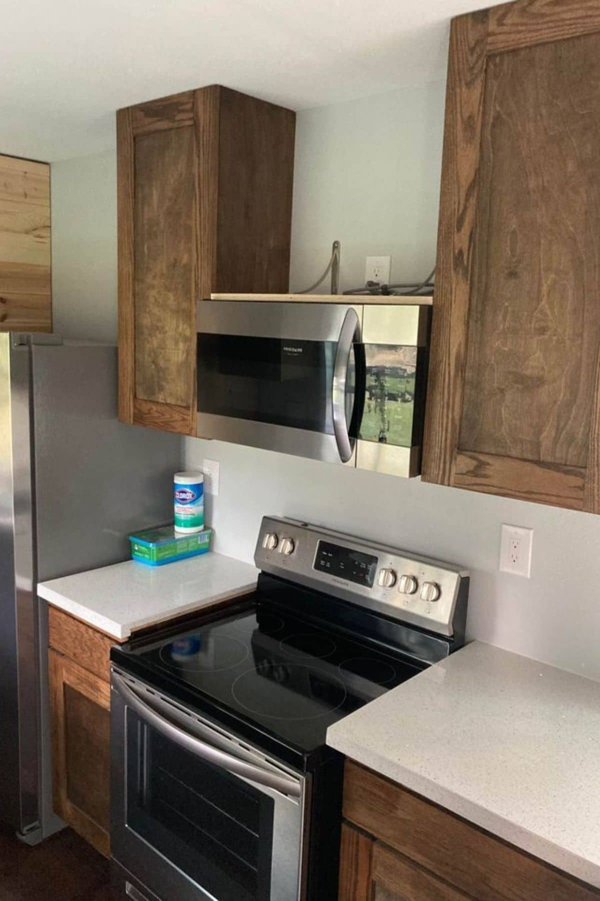Stainless steel electric range in between white counters in kitchen with wood cabinets