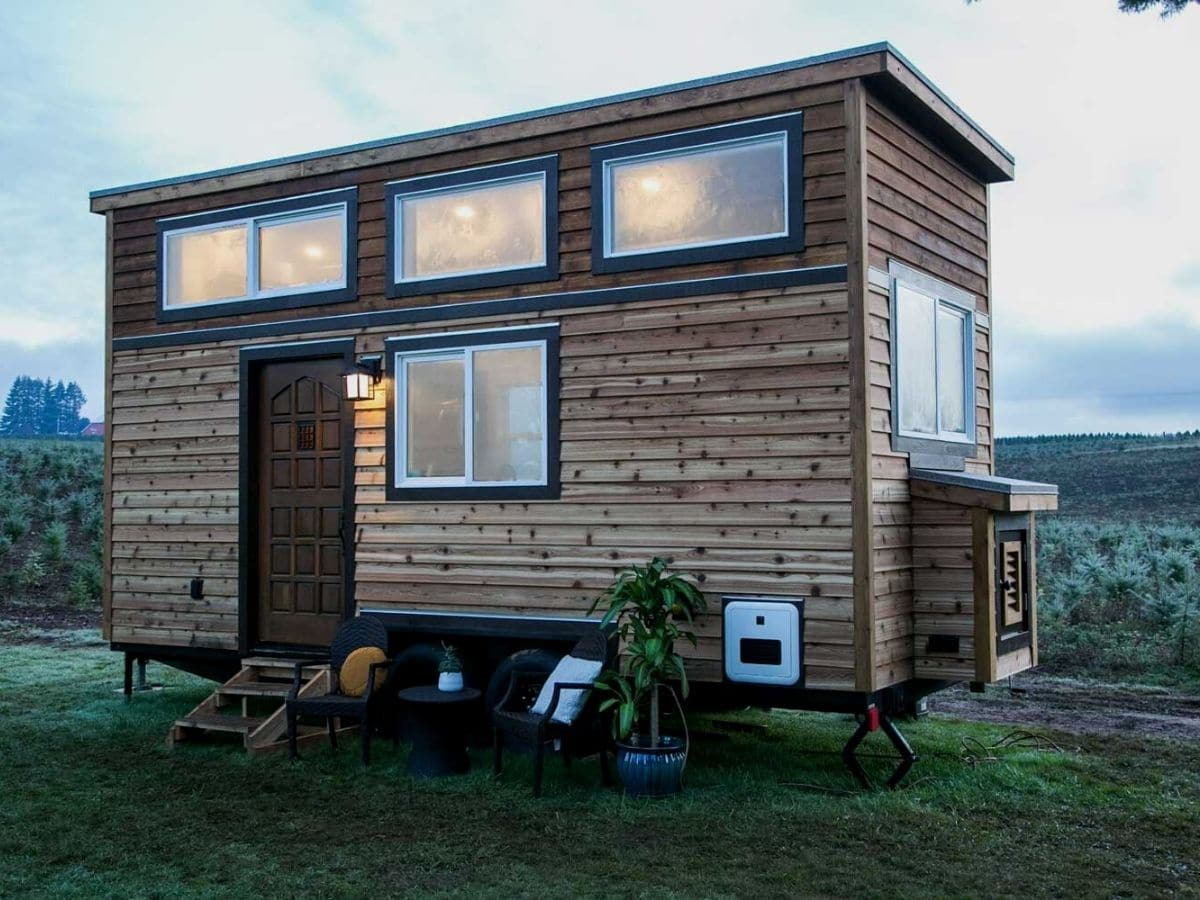 Wood siding on small tiny house with three large windows at top
