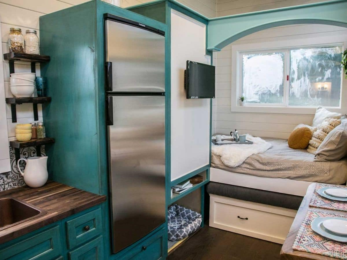 Teal cabinets around stainless steel refrigerator next to white cabinet