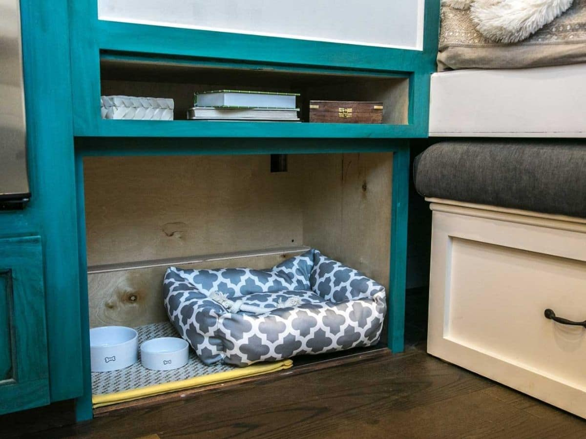 Dog bed underneath white and teal cabinet
