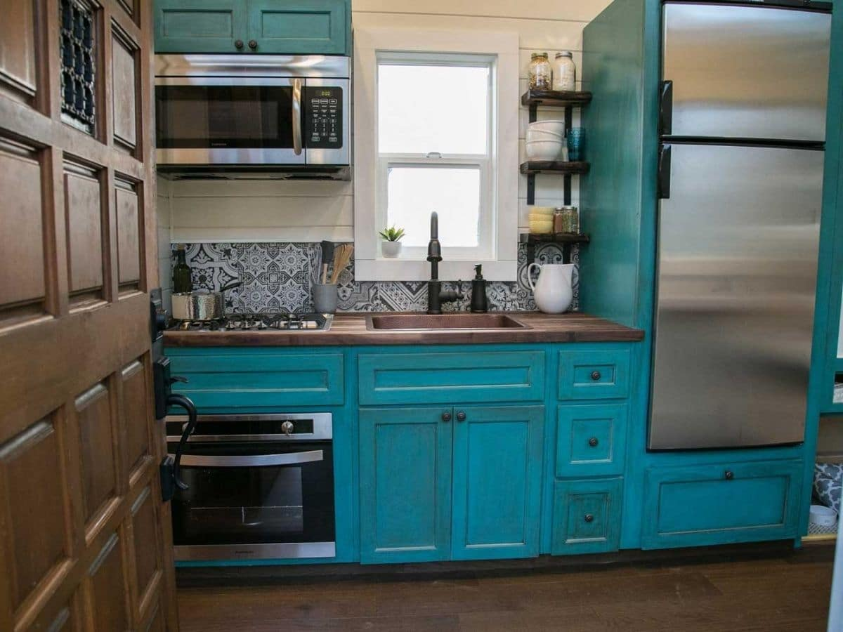 Teal cabinets in kitchen with stainless steel stove and refrigerator