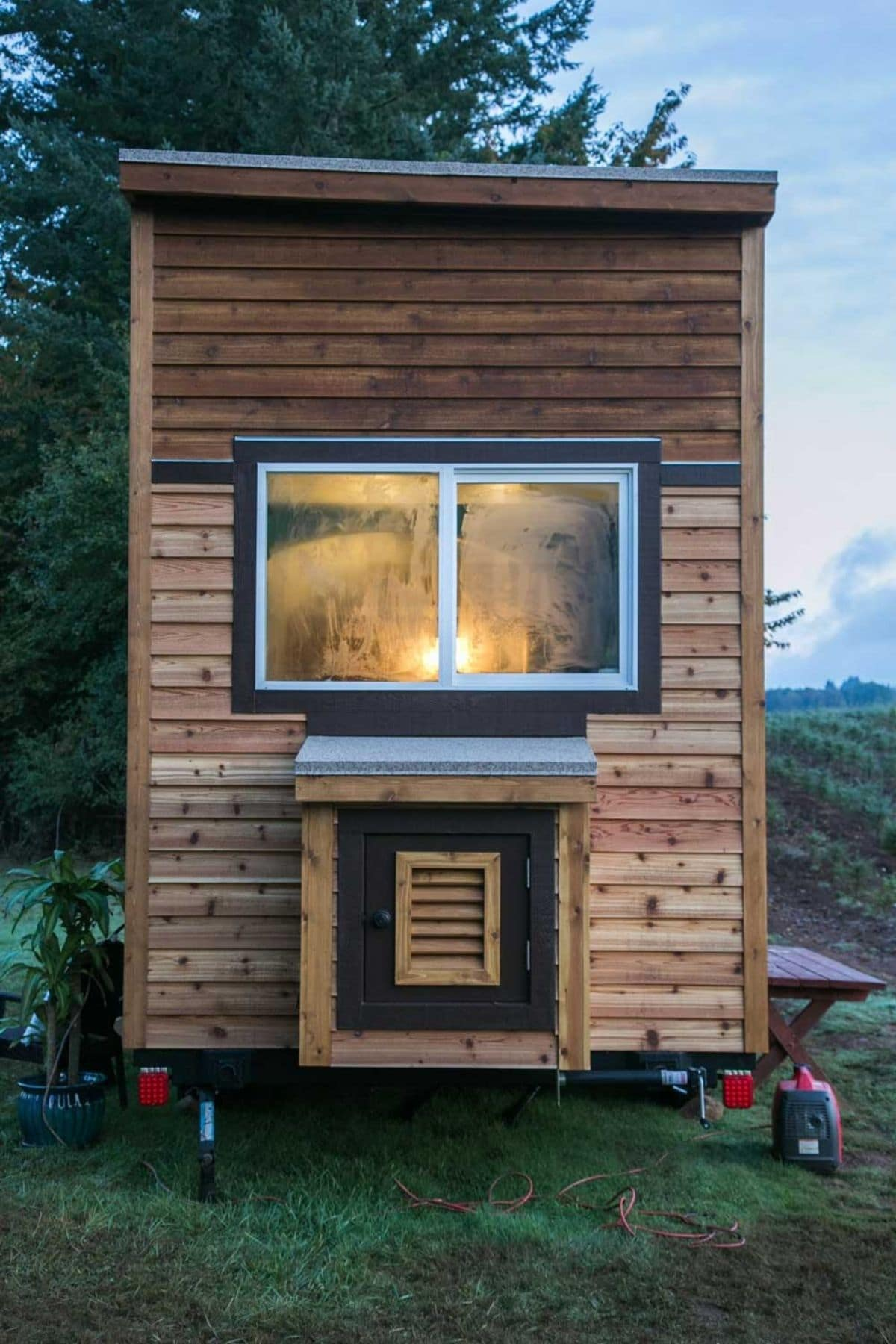 End of wood siding archway tiny home with double window