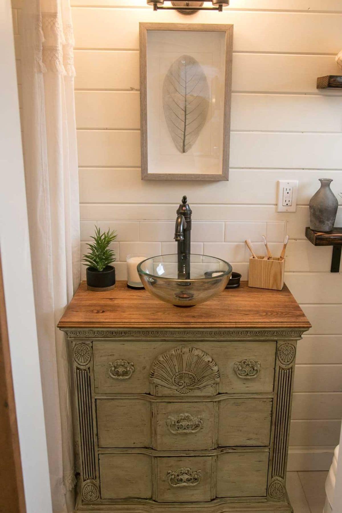 Olive green custom vanity below glass bowl sink