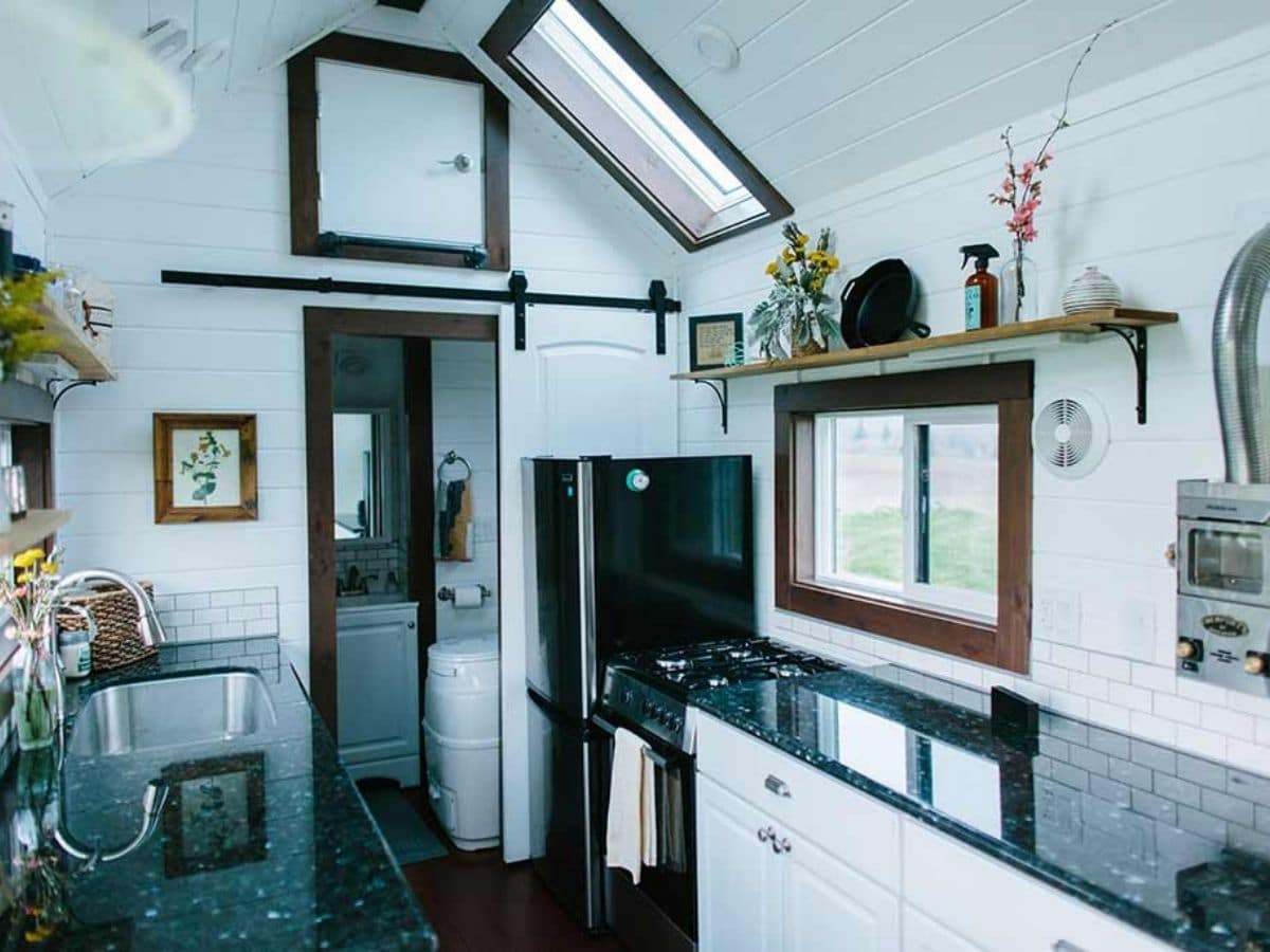 Dark kitchen counter with white cabinets in tiny house