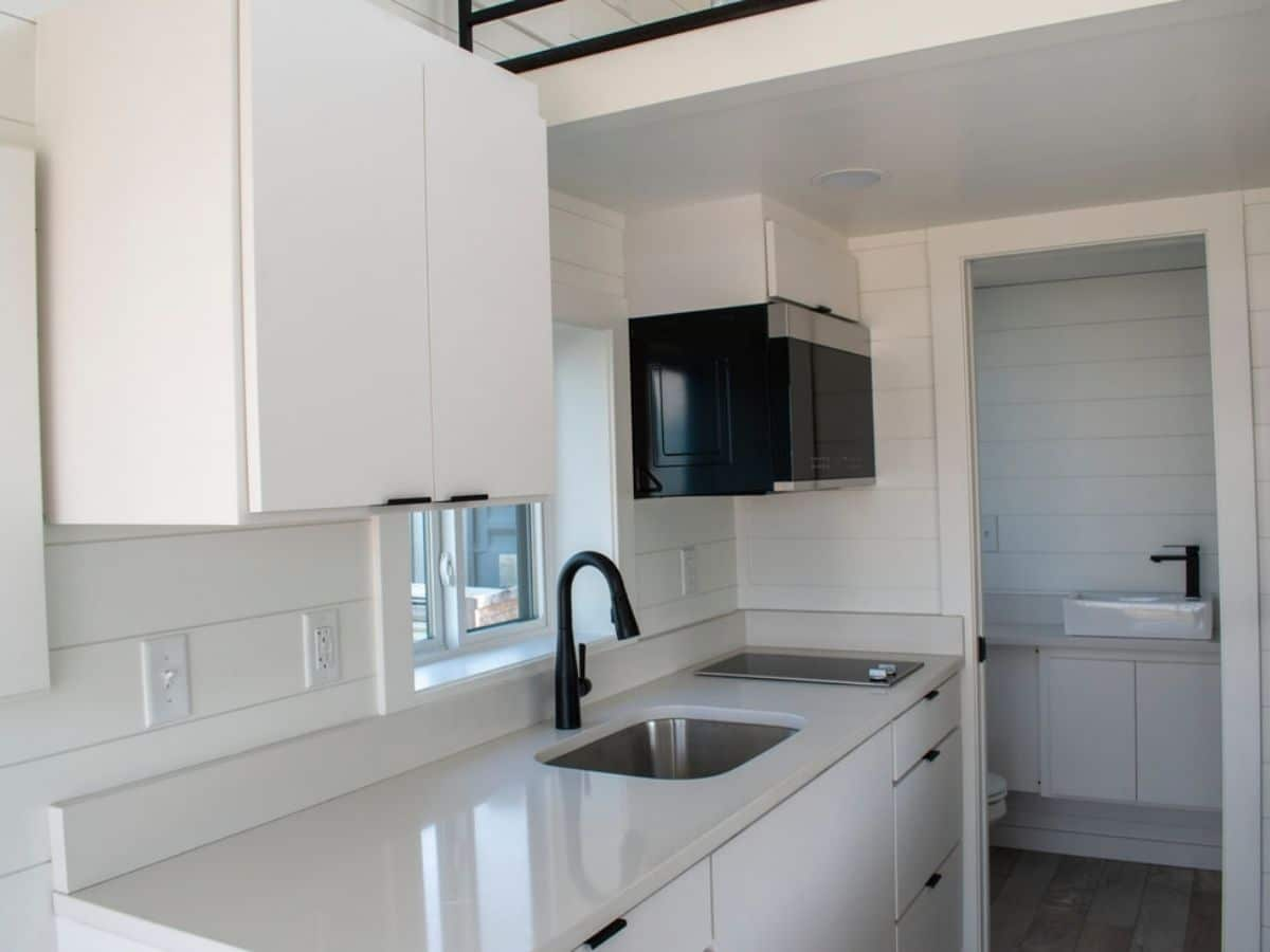 stainless steel sink in white counter above white cabinets next to white walls