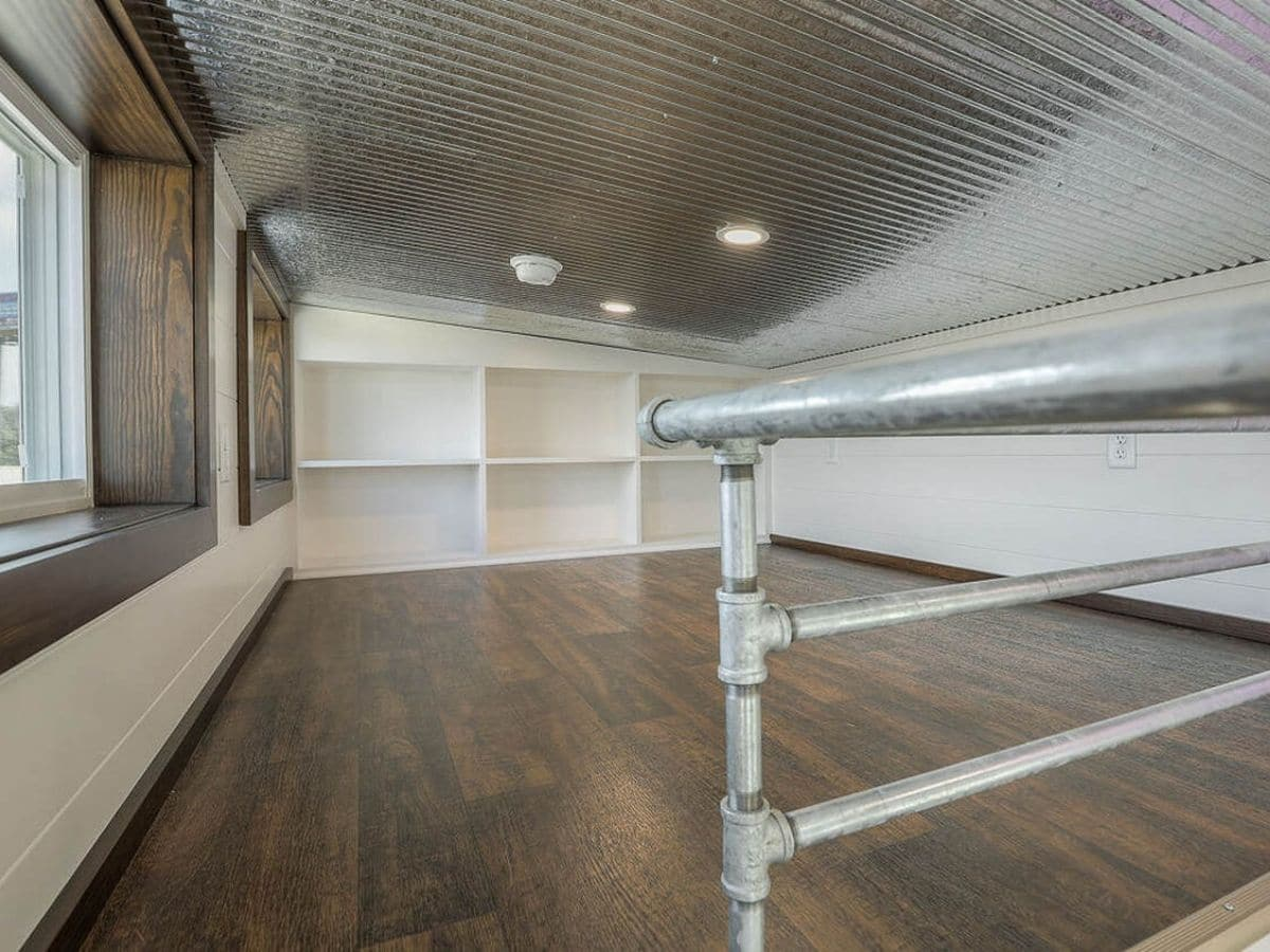 Loft with wood floors metal railing and white built in shelves at back