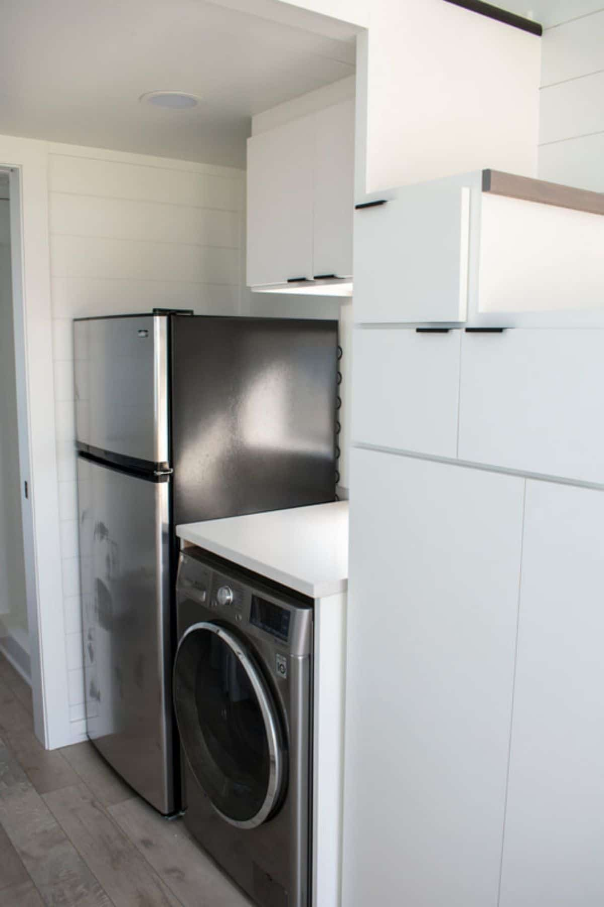 Stainless steel refrigerator next to white cabinets and washing machine