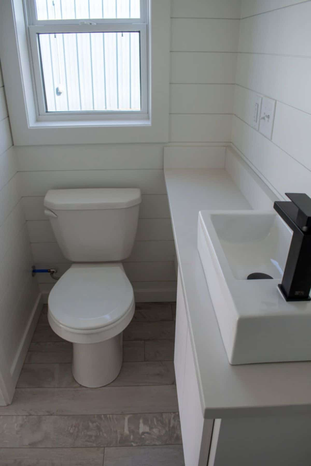Flush toilet on wood floors next to white acbinet and sink