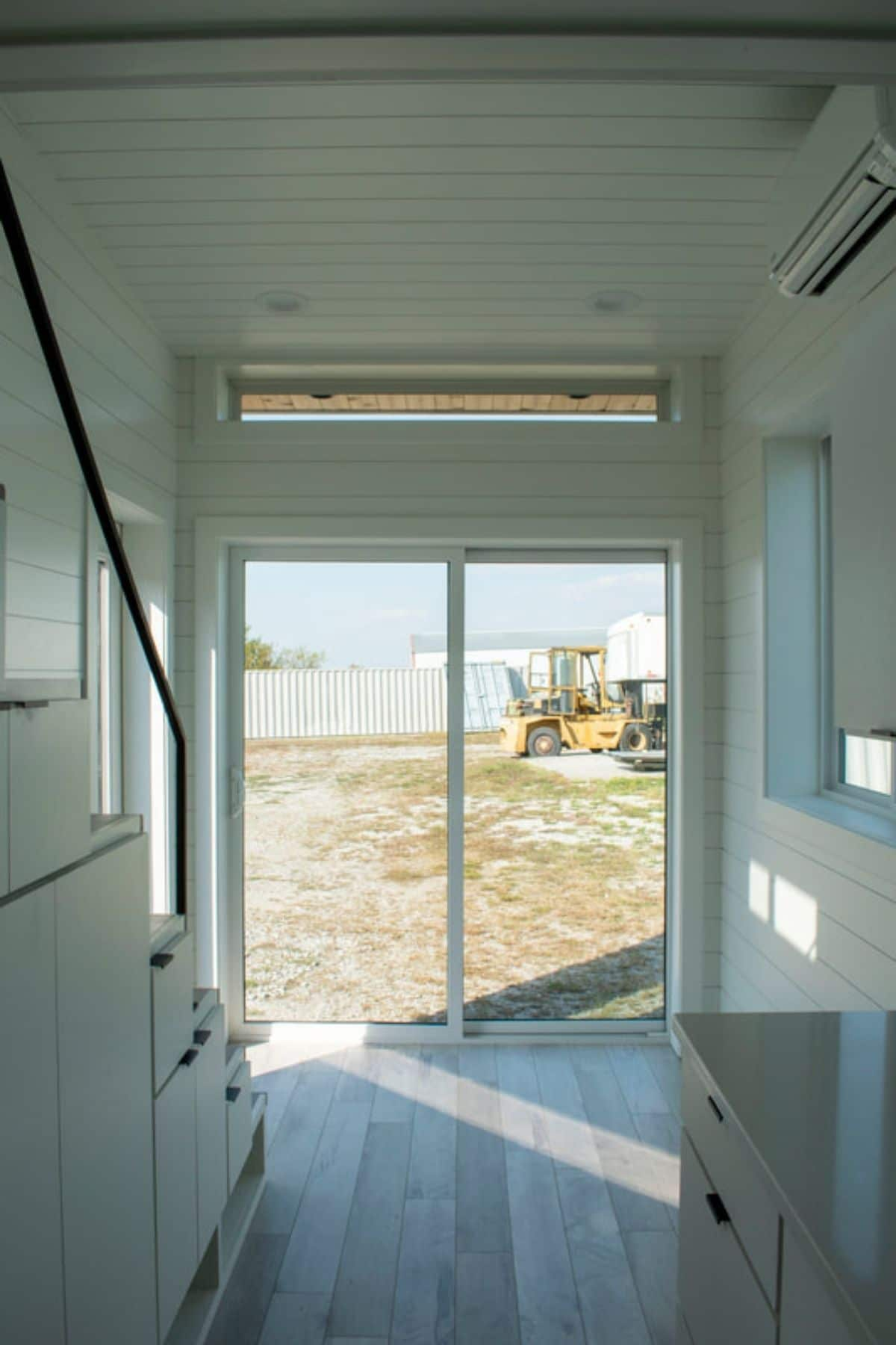Full wall picture windows at end of white interior of tiny home