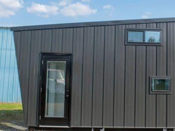 Gray tiny home with black trim around door
