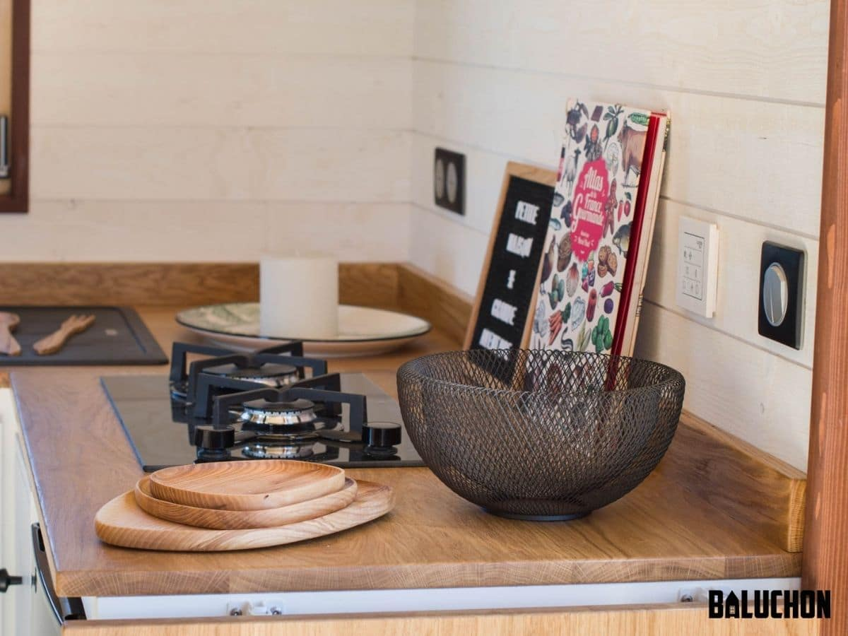 Wire bowl and wooden plates on counter next to gas stove