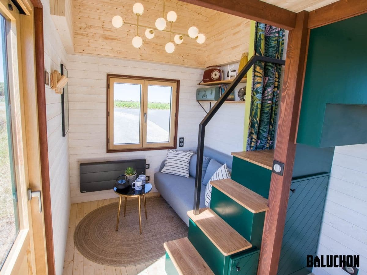 View into tiny home living room with blue sofa and chandelier light