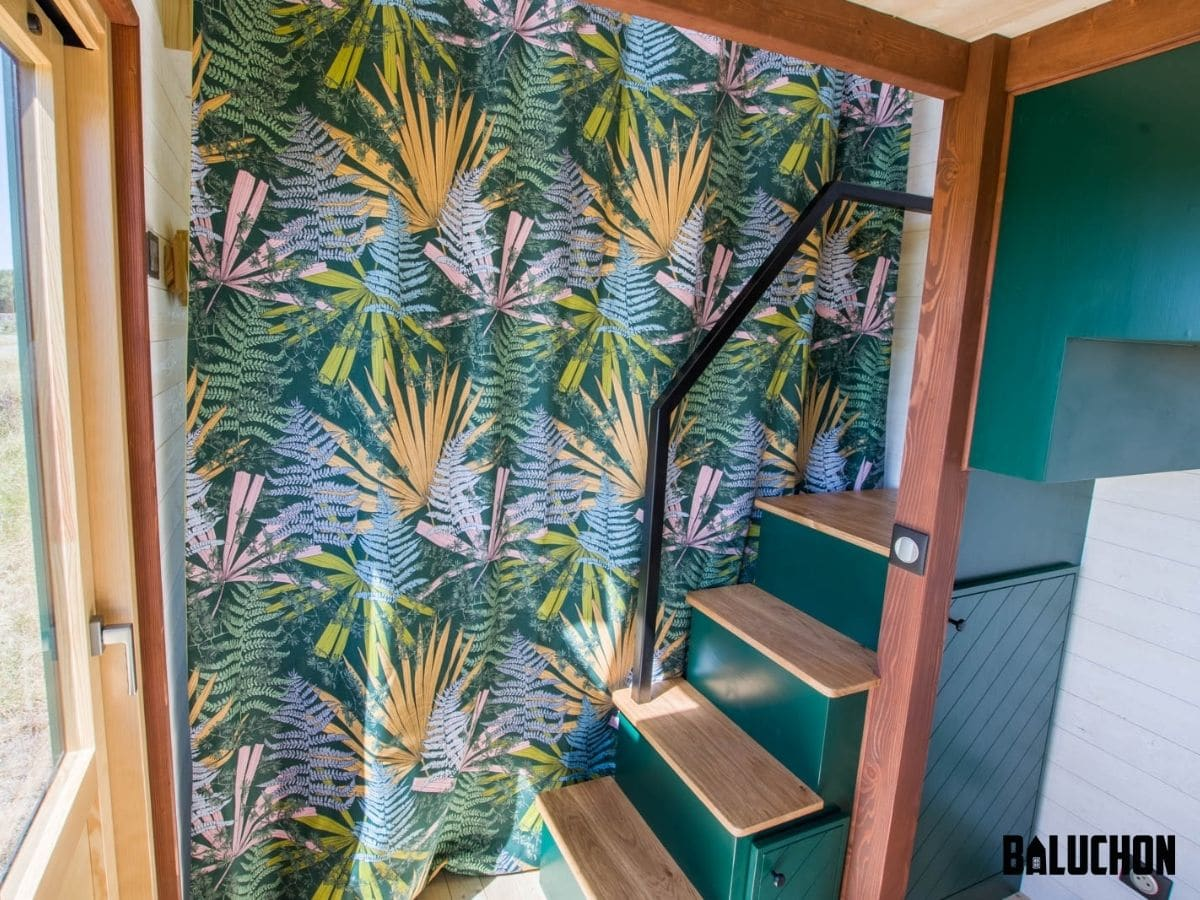 Floral curtain pulled across entry to living room next to green stairs