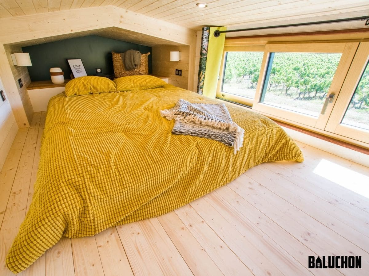 Yellow bedding on mattress in loft with natural wood floor and large windows