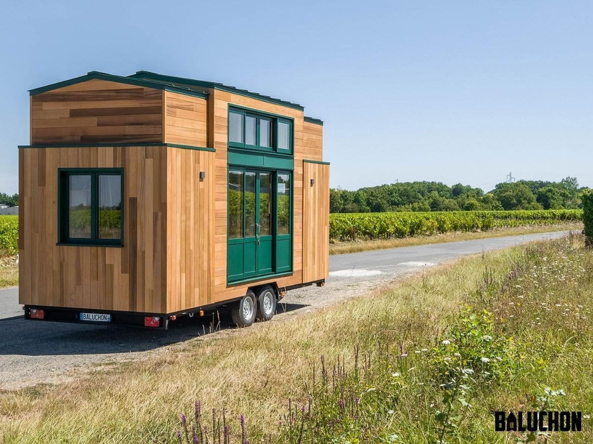 Wood siding and green trim on tiny home on drive