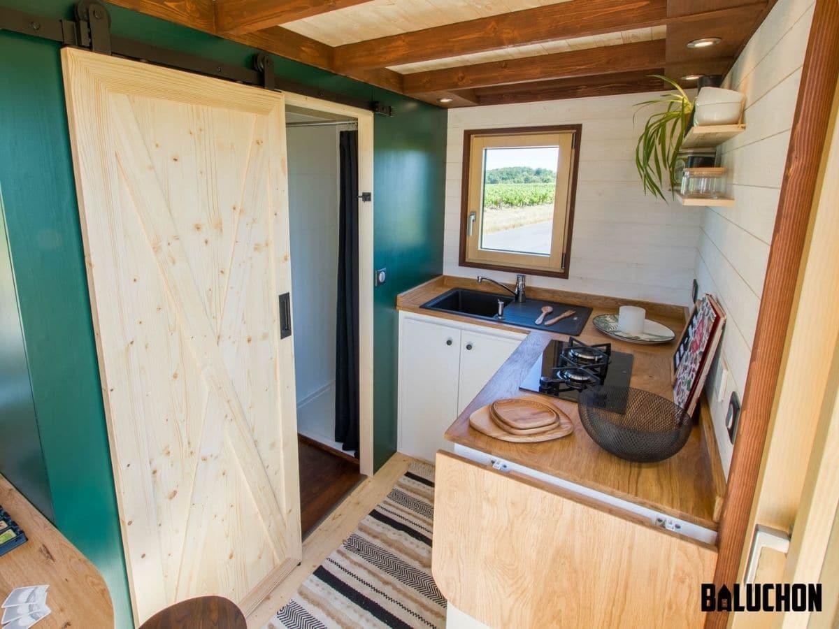 Bathroom door open next to kitchen