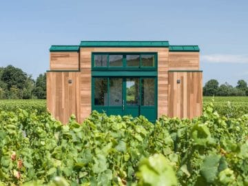 Wood siding with green trim on tiny house in field of grass