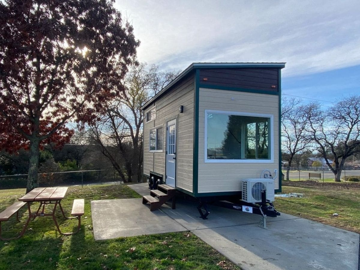 Side of tan and blue tiny home on concrete pad