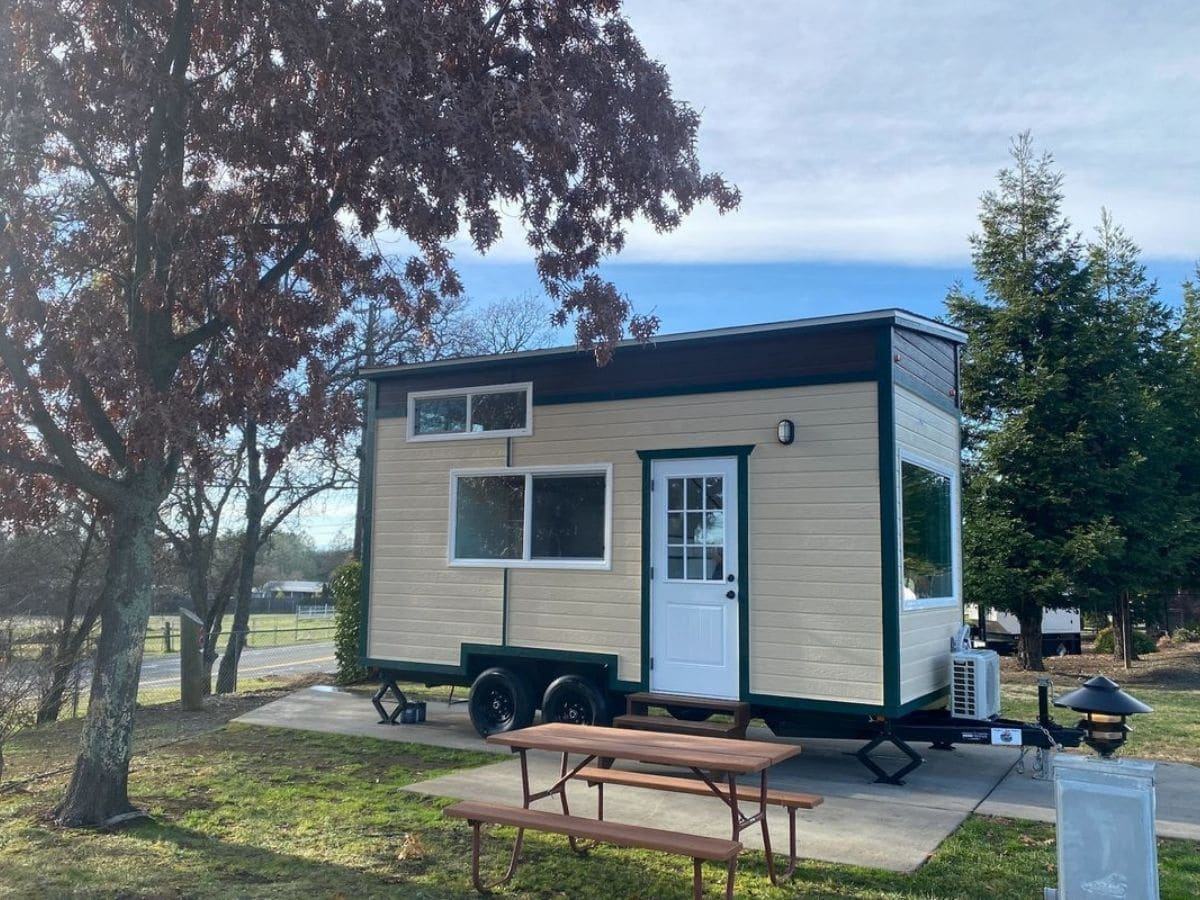 Tiny Victorian tiny home with tan siding and blue trim on lot by picnic table