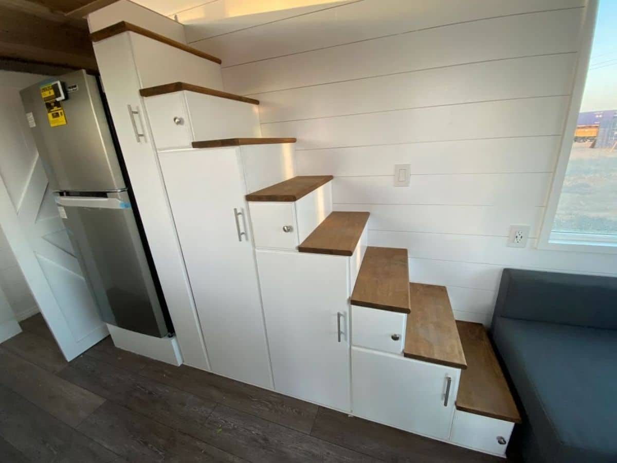 side of white stairs showing doors for storage underneath
