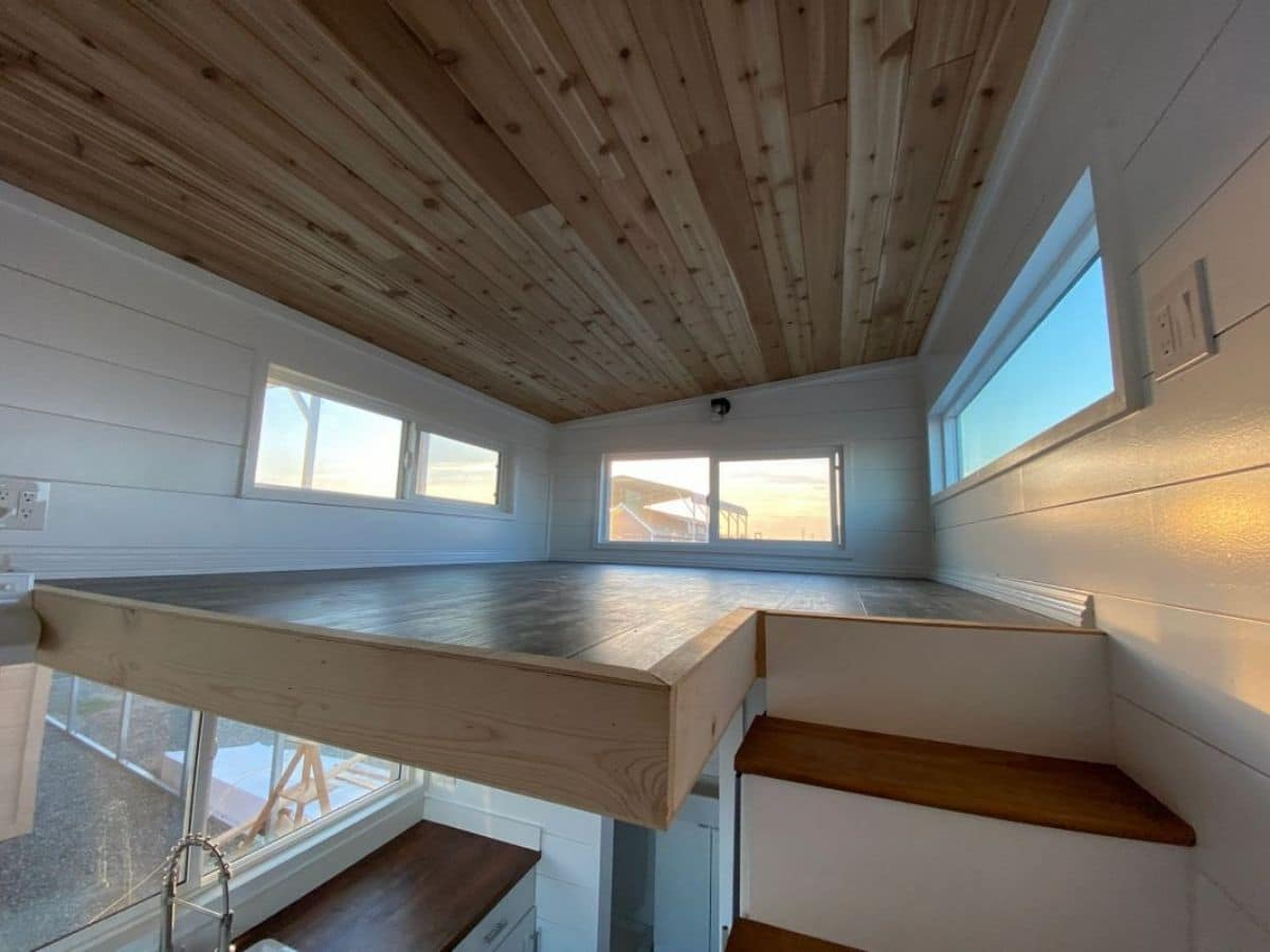 View into loft with wood floor and ceiling and white walls with windows on all sides